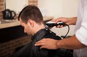 stock photo of clippers  - Male hairstylist using hair clippers on a customer at a hair salon - JPG