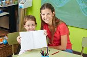 Proud child showing drawing in kindergarten with nursery teacher