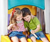 Boy and girl as children friends playing together in a kindergarten