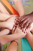 Team of kids stacking their hands in a kindergarten group
