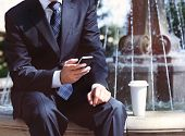 image of fountains  - Close up of the hands of the businessman with a mobile phone and coffee near the fountain - JPG