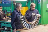 Mechanics assembles turbine for aviation engine