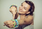 Young Beautiful Brunette With Colorful Rubber Bracelets On Her Hands