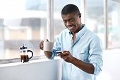 young african businessman with coffee and mobile phone at window in morning
