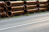pic of waterspout  - Stacks of pipes next to asphalt road - JPG