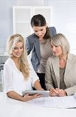 Team: Successful business team of woman in the office talking together looking at tablet computer.