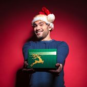 Handsome young santa giving you a green gift while smiling. On red backgrpund.
