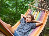 Boy lying in hammock outdoors