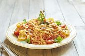 Pasta with tomatoes, ham, capers and cheese