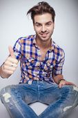 Close up picture of a young fashion man smiling for the camera while showing the thumbs up sign.