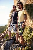 Two men with a safety harness on holding their rock climbing equipment standing on a rock in the mountain