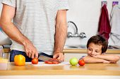 young boy watches dad prepare healthy food for school