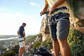 Cropped image of two men putting on their harness and rock climbing equipment