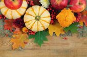 yellow pumpkins and leaves on wooden background