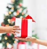 holidays, present, childhood and happiness concept - close up of child and mother hands with gift box over christmas tree lights background