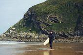 Young surfer walking to the waves along beautiful shore