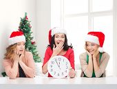winter, holidays, time and people concept - smiling women in santa helper hats with clock over living room and christmas tree background