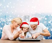 food, family, christmas, happiness and people concept - smiling family in santa helper hats with glaze and pan cooking over snowy city background