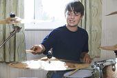 stock photo of drum-kit  - Boy Enjoying Playing Drum Kit At Home - JPG