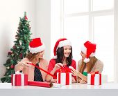 holidays, celebration, decoration and people concept - smiling women in santa helper hats with decorating paper and gift boxes over living room and christmas tree background