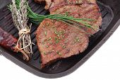 roasted beef meat fillet on bbq pan with cayenne pepper isolated on white background