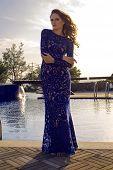 Pretty Brunette In Luxurious Lace Dress Posing Beside A Swimming Pool