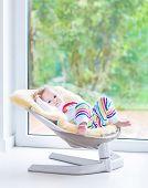 Cute little girl relaxing in a swing next to a big window