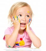 Little girl is holding her face in astonishment while playing with paints, isolated over white