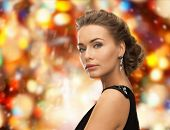 people, holidays, christmas and glamour concept - beautiful woman in evening dress wearing earrings over red lights background
