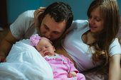 Image of young caucasian family indoor. Father, mother and cute little girl