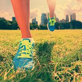 Healthy lifestyle runner - running shoes on woman athlete running shoes on grass. Female jogger womens shoes in Central Park, New York City.