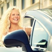 Woman driving car. Female driver in new car convertible smiling happy. Beautiful young woman in her 20s.