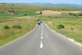 straight road crosses rural area of Pester plateau, Serbia