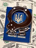 International Ukrainian passport with handcuffs on US dollars background