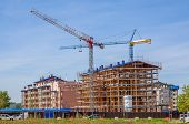 View of cranes and new modern residential buildings on construction site in Alba, Italy.