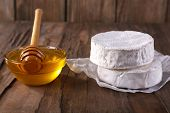 Camembert cheese on paper and honey in glass bowl on wooden background