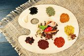 Painting palette with various spices and herbs, on wooden background