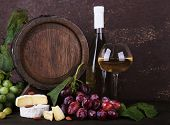 Wine in bottle and in goblet, Camembert and brie cheese, grapes and wooden barrel on wooden table on wooden background