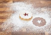 picture of linzer  - Christmas Linzer Cookie with powdered sugar on a wooden background - JPG