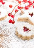 foto of linzer  - Christmas Tree Linzer cookie with powdered icing sugar and red decorations in the background - JPG