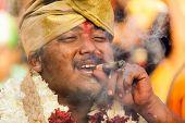 BATU CAVES, MALAYSIA, FEBRUARY 07, 2012: Hindu devotee smoking a cigar and laughing during annual Thaipusam religious festival in Batu Caves, near Kuala Lumpur, Malaysia.