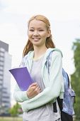 Portrait of happy young woman holding book at college campus