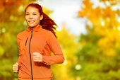 Runner woman running in fall autumn forest. Female fitness girl jogging on path in amazing fall foliage landscape nature outside.