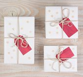High angle image of Christmas presents wrapped in white paper and tied with white string. Red gift t