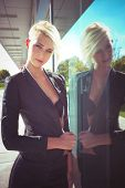 young blue eyes woman with short blonde hair in elegant  black blazer reflection in glass