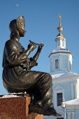 Statue Of Girl Playing Flute With Church In Background, Russia