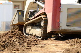 foto of skid-steer  - Infrastructure excavation building contractors smoothing dirt over water lines in a utility trench at a commercial residential development - JPG