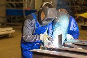 picture of welding  - Two steel construction workers welding metal pieces - JPG