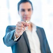 Businessman Holding Up A Key
