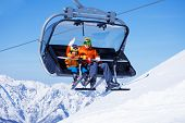 pic of ropeway  - Close view of young man and little boy skiers sitting on the chair on ropeway lift with high mountain with snow on background - JPG